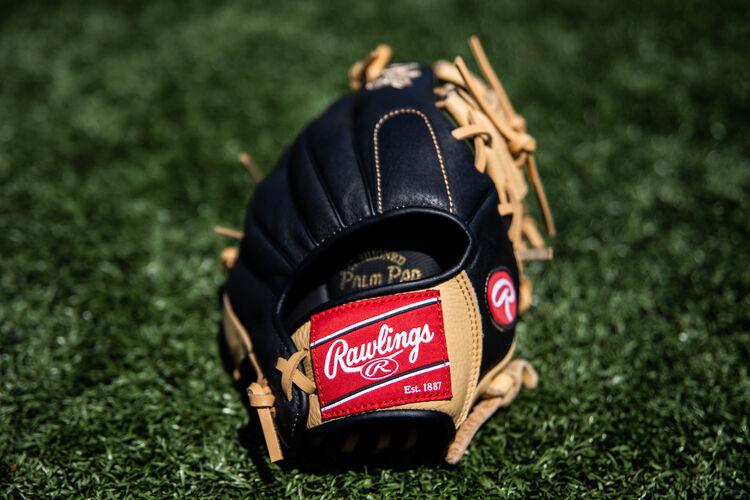 Rawlings patch on a Rawlings Prodigy glove sitting on a field- SKU: P115CBI