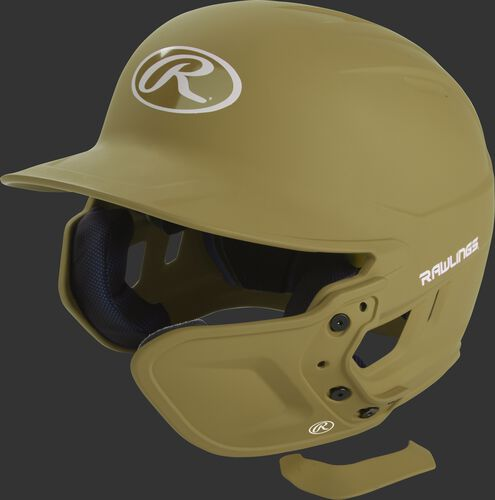 A Vegas gold MEXTR attached to a Mach batting helmet with the removable TPU piece off to show the hardware