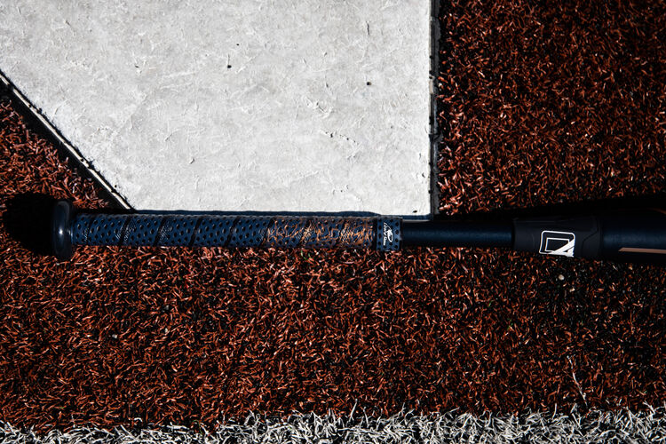 Handle of a Rawlings Quatro Pro fastpitch bat lying next to home plate - SKU: FPZP9
