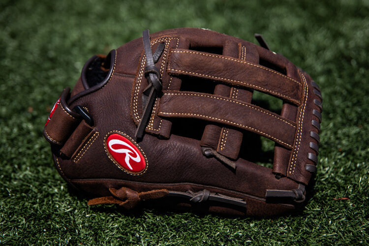 A brown Player Preferred H-web glove lying on a field - SKU: P130HFL