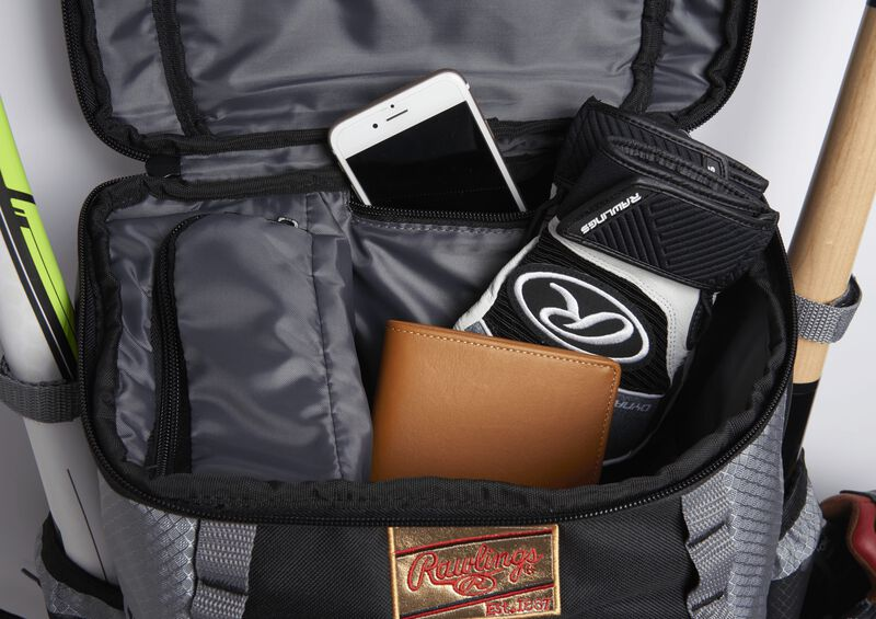 The top compartment on black/gray Gold Glove Series backpack with a wallet, phone and batting gloves