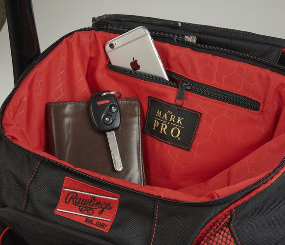 "Top compartment of a scarlet/black R600 Players team bag with a phone, wallet and keys and ""The Mark of a Pro"" patch"