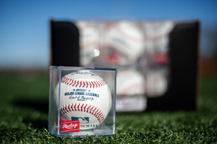 An MLB ball in a display cube sitting in front of a box of a dozen balls on a field - SKU: ROMLB-R