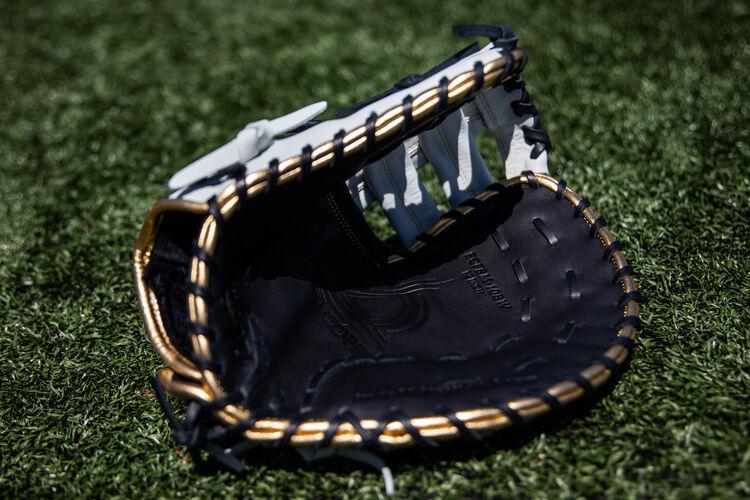 An Encore first base mitt lying on a field showing the black palm - SKU: ECFBM-10BW