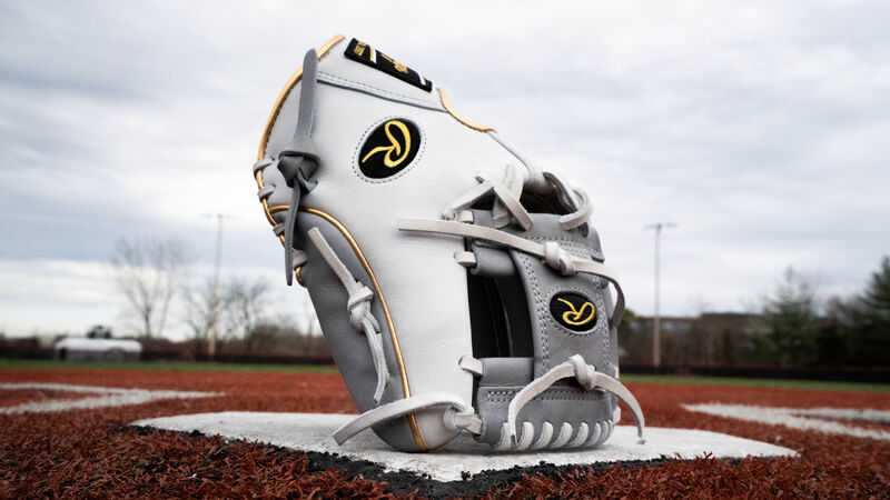 A grey/white 2020 Heart of the Hide exclusive infield glove standing up on home plate of a field - SKU: PRO204W-2GW
