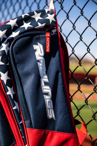 Side of a USA Rawlings Legion backpack on a fence with the Rawlings logo on the shoe compartment - SKU: LEGION-USA
