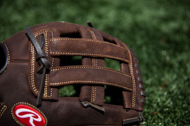 Brown H-web on a Rawlings Player Preferred 13-inch glove lying on a field - SKU: P130HFL