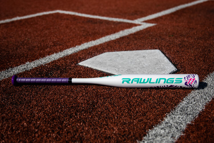 A Rawlings Ombre fastpitch softball bat lying on a field next to home plate - SKU: FPZO11