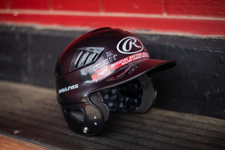 A Rawlings Coolflo baseball batting helmet sitting on the bench in a dugout - SKU: RCFH