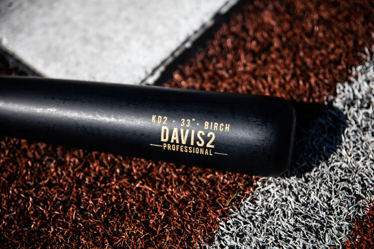 Black barrel of a Rawlings Pro Label Khris Davis bat next to home plate - SKU: KD2PL