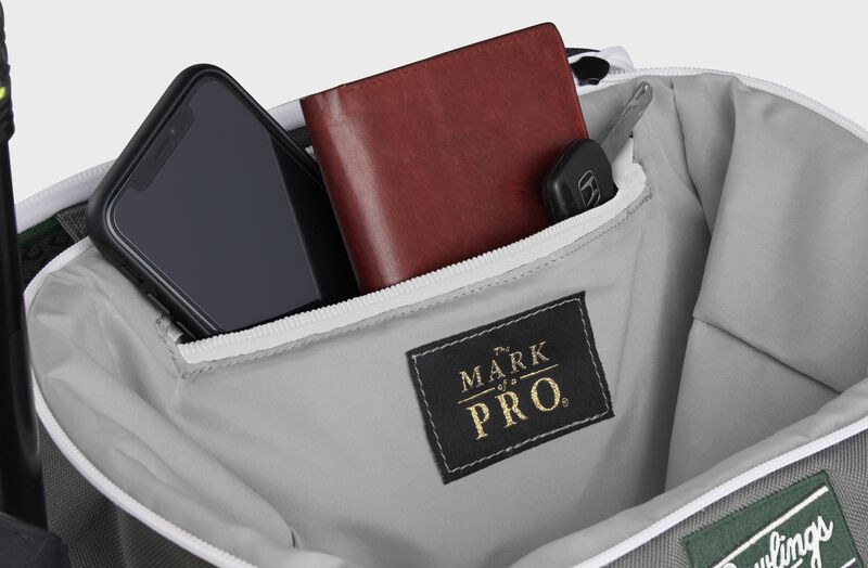 Zippered pocket in the top storage compartment of a dark green Impulse backpack with a phone, wallet and keys - SKU: IMPLSE-DG