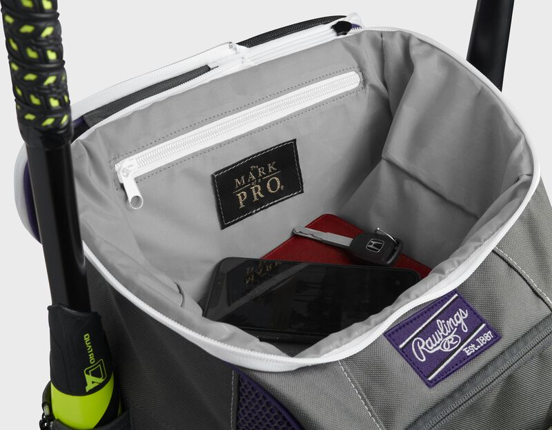 """Top compartment of a purple Impulse bag with a phone, keys and black """"The Mark of a Pro"""" patch - SKU: IMPLSE-PU"""
