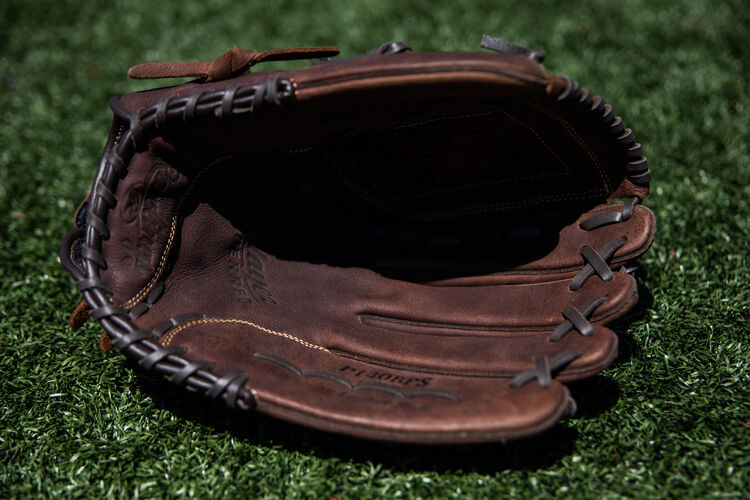 Brown palm of a Player Preferred softball glove lying on a field - SKU: P140BPS