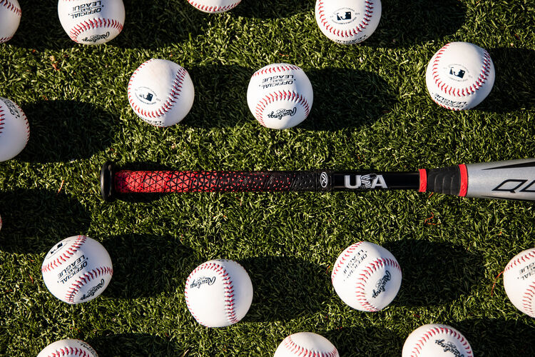 Handle of a -8 USA baseball Quatro Pro bat on a field with baseballs - SKU: US1Q8
