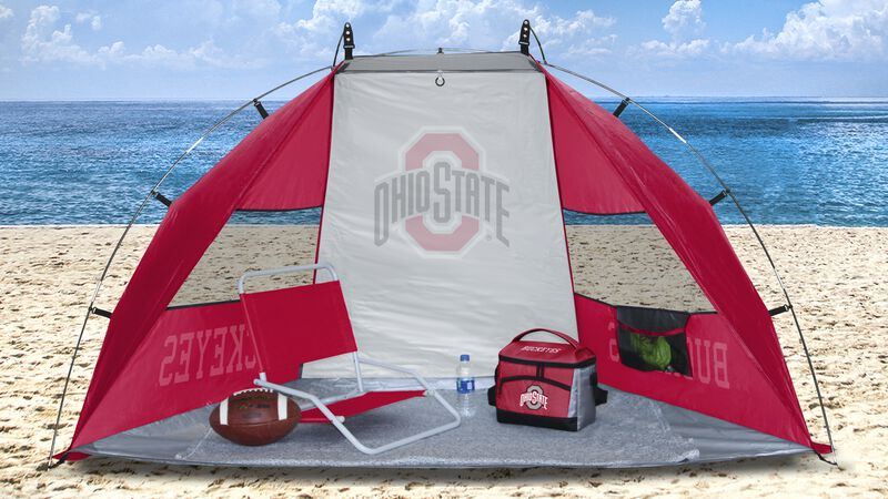 An Ohio State Buckeyes sun shelter set up on a beach with a cooler, football, chair and water bottle - SKU: 00973042111