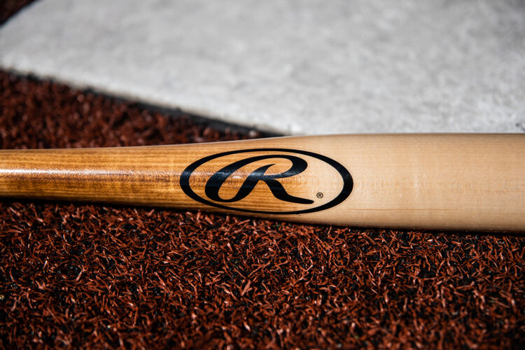 Black Oval-R on a natural Rawlings Manny Machado wood bat lying next to home plate - SKU: MM8PL