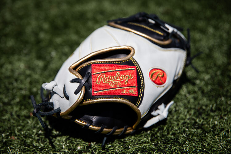 A red Rawlings patch on a 32-inch Encore catcher's mitt lying on a field - ECCM32-23BW