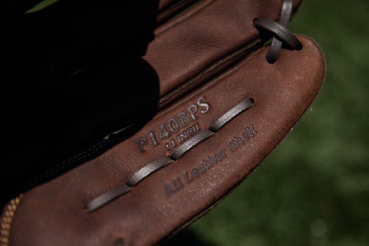 Brown pinkie of a Rawlings Player Preferred softball glove on a field - SKU: P140BPS