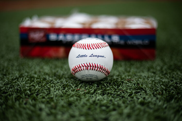 A Rawlings Little League competition grade baseball lying on a field in front of a box of balls - SKU: RLLB1