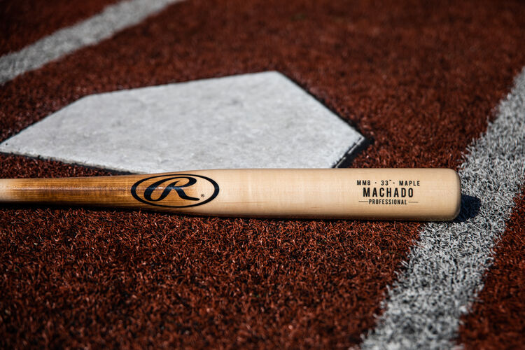 A natural wood colored Manny Machado wood bat lying at home plate - SKU: MM8PL