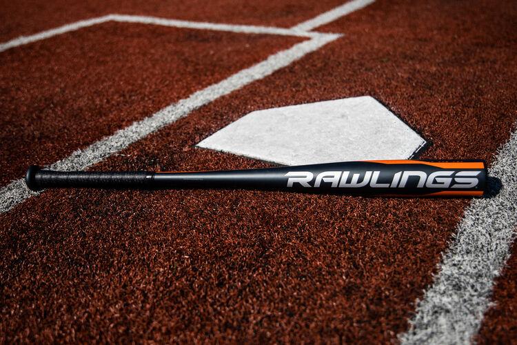 A Rawlings 2020 Impact BBCOR bat lying on a field next to home plate - SKU: BBZI3