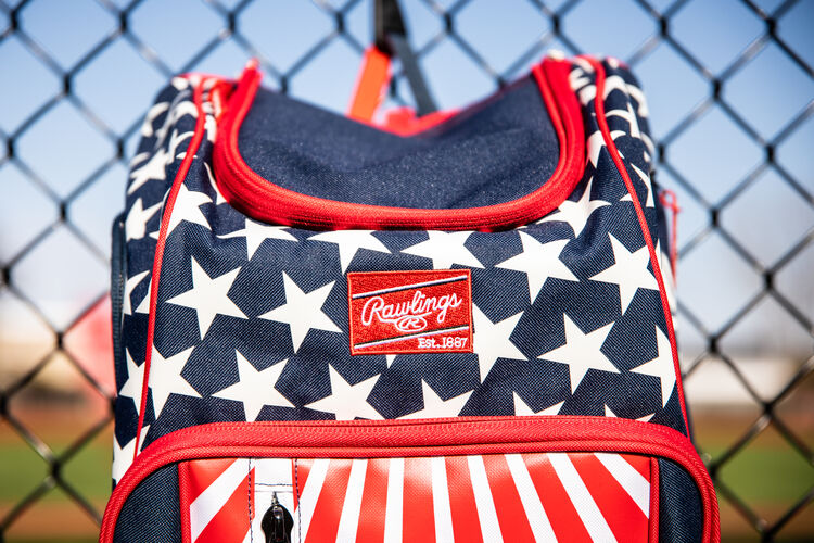 The red Rawlings patch on a USA Rawlings Legion backpack hanging on a fence - SKU: LEGION-USA