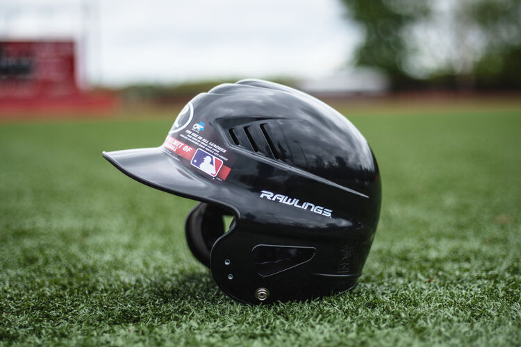 Left side of a black Rawlings Coolflo batting helmet sitting on a field - SKU: RCFH