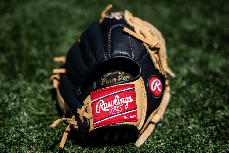 Rawlings patch on a Prodigy infield glove lying on a field - SKU: P110CBB