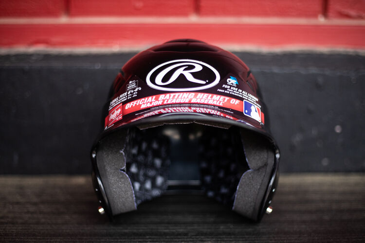 Front of a Rawlings Coolflo baseball helmet sitting on a bench in a dugout - SKU: RCFH
