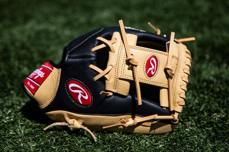A Prodigy I-web infield glove lying on a field - SKU: P115CBI
