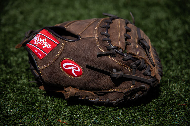 A brown Player Preferred catcher's mitt lying on a field - SKU: PCM30