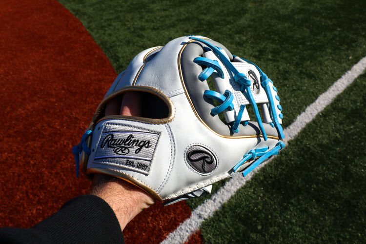A Rawlings Heart of the Hide ColorSync 5.0 I-web infield glove on a person's hand with a field in the background - SKU: PRO314-2GW